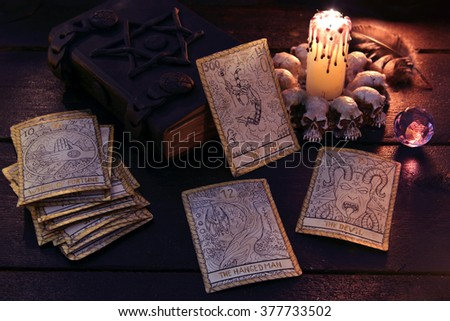 The tarot cards with crystal, candle and book. Halloween and magic still life, fortune telling seance or black magic ritual with mysterious occult and esoteric symbols, divination rite  - stock photo