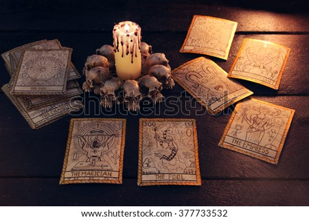 The tarot cards with evil candle. Halloween and magic still life, fortune telling seance or black magic ritual with mysterious occult and esoteric symbols, divination rite  - stock photo
