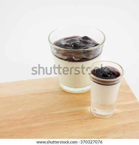 The tasty homemade blueberry panna cotta (Italian pudding dessert) in the small glass on wooden board. - stock photo