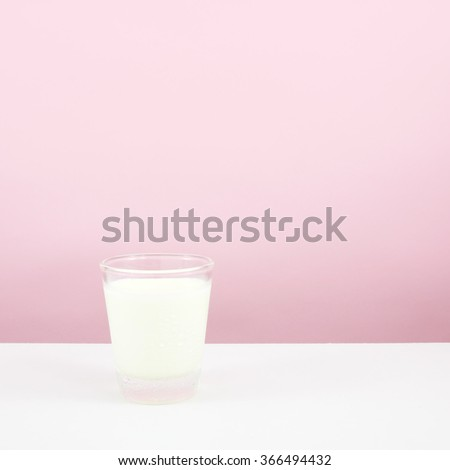The tasty homemade panna cotta (Italian pudding dessert) in the small glass on white table. - stock photo