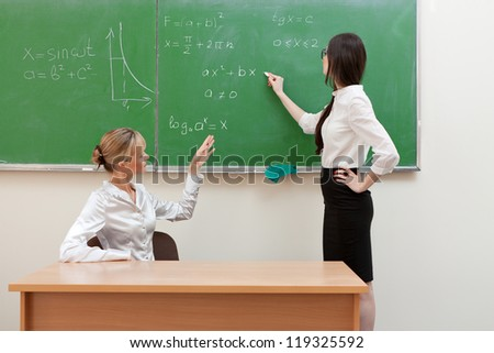 The teacher in the classroom on blackboard background.