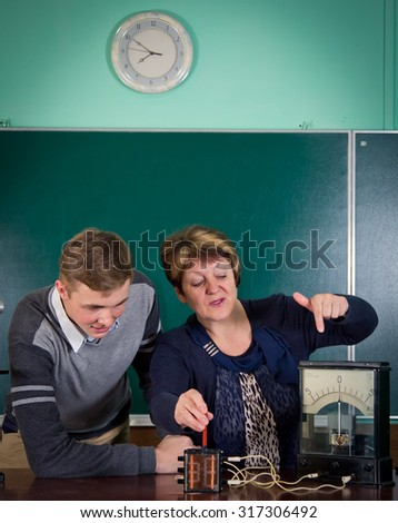 The teacher of physics explains to the pupil interaction of a magnetic field and electric field. Electrical engineering  bases - stock photo