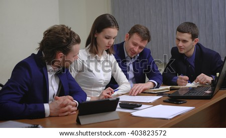 The team of young businesspeople. The meeting, brainstorming. In the office. Smooth motion
