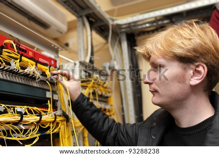 The technician connecting optical connector at the server room - stock photo