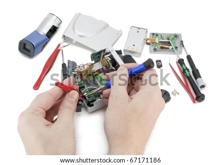 The technician repairs a modern  mass production digital video move camera. Isolated on white - stock photo