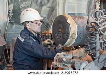 The technician repairs the industrial mechanism - stock photo