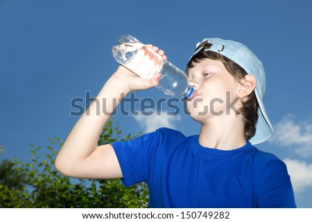 The teenager drinks water from a bottle against the sky