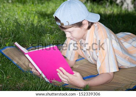 The teenager in cap lays on grass with the book in hands - stock photo