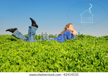 The teenager lays in a spring grass and dreams about home - stock photo