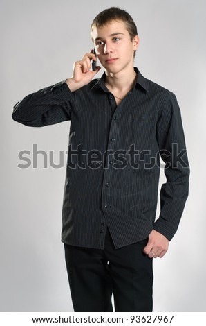 The teenager speaks on the phone - stock photo
