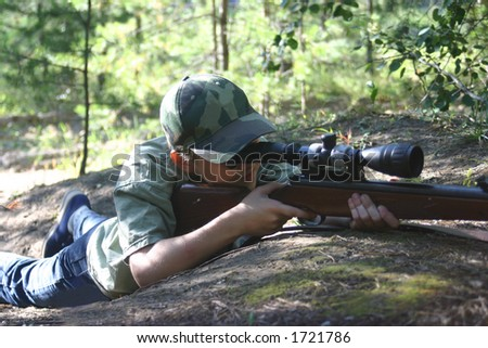 The teenager with a rifle. - stock photo