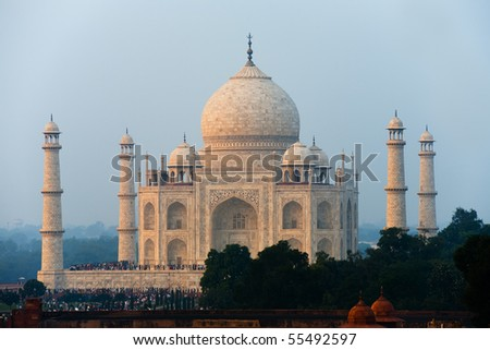 The telephoto distant Taj Mahal white marble reflects orange glowing sunset colors in the evening in Agra, India. Horizontal copy space - stock photo