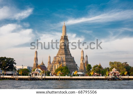 The Temple of Dawn, Wat Arun, on the Chao Phraya river and a beautiful blue sky in Bangkok, Thailand. Horizontal with copy space - stock photo