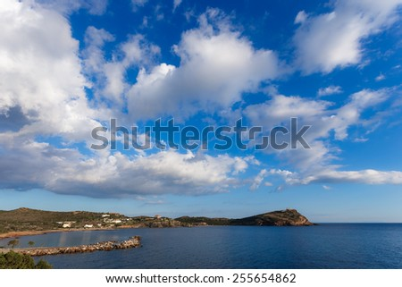 The Temple of Poseidon at Sounio, Greece against a blue cloudy sky, shot taken from accross the bay, long exposure photo