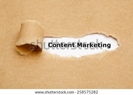 The text Content Marketing appearing behind torn brown paper.  - stock photo