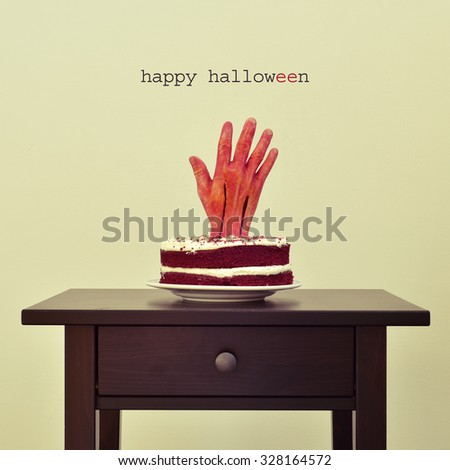 the text happy halloween and a red velvet cake topped with a bloody hand, on a table - stock photo