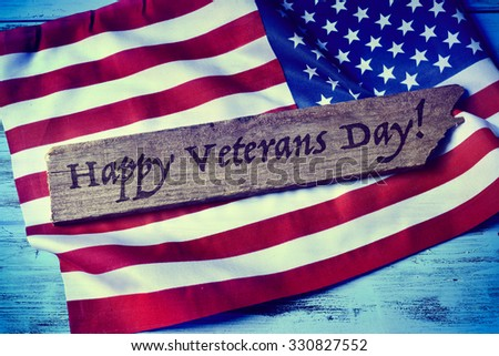 the text happy veterans day written in a piece of wood and a flag of the United States, on a blue rustic wooden background - stock photo