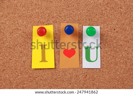 The text 'I love U' in cut out magazine letters pinned to a cork board. - stock photo