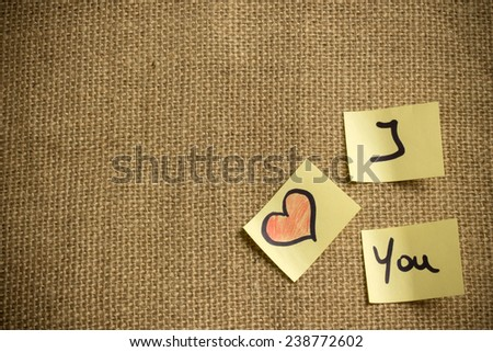 the text I Love You on little  peaces of paper over a canvas background - stock photo
