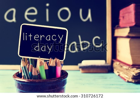 the text literacy day written in a chalkboard, in a retro and rustic classroom, with a filter effect - stock photo