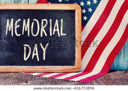 the text memorial day written in a chalkboard and a flag of the United States, on a rustic wooden background - stock photo