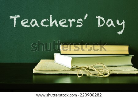 the text Teachers Day written with chalk on a green chalkboard and some books on a desk - stock photo