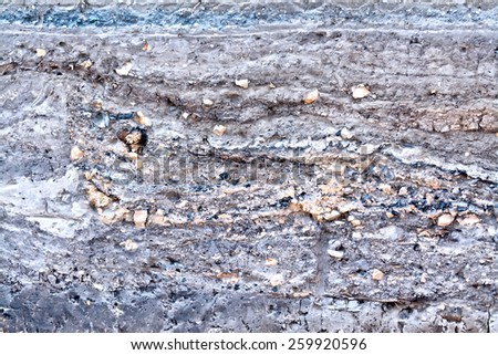 The texture of the layers of gray, brown soil and stones - stock photo