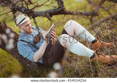 The theme is Oktoberfest, a guy in a beautiful mountain area lies in nature and looks at the tablet
