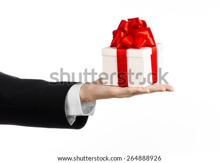 The theme of celebrations and gifts: a man in a black suit holding a exclusive gift wrapped in white box with red ribbon and bow, the most beautiful gift isolated on white background in studio