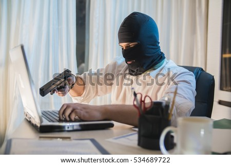 the thief hacker working on laptop in the night stealing data