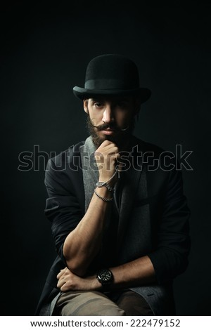 The thoughtful brutal bearded man in a black bowler hat touching his beard