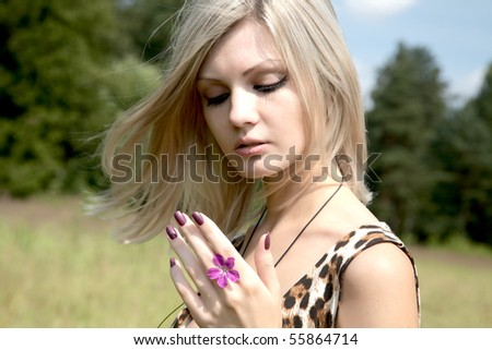 The thoughtful girl with a field flower in summer day - stock photo