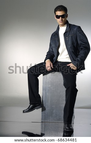 The thoughtful young man in sunglasses on a cube - stock photo