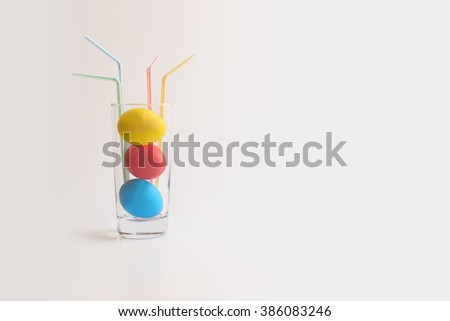 The three Easter eggs of red, blue and yellow colors in the glass with the four cocktail straws of  red, blue, green and yellow colors on a warm gradient background. - stock photo