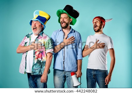 The three football fans singing the national anthem over blue - stock photo