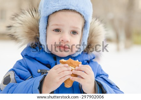 The three-year girl is outside in the winter eating a muffin