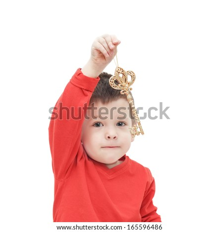 the three-year-old kid lifts a gold key over the head - stock photo