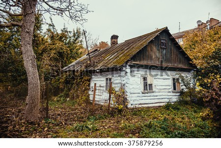 The thrown old wooden house in the city - stock photo