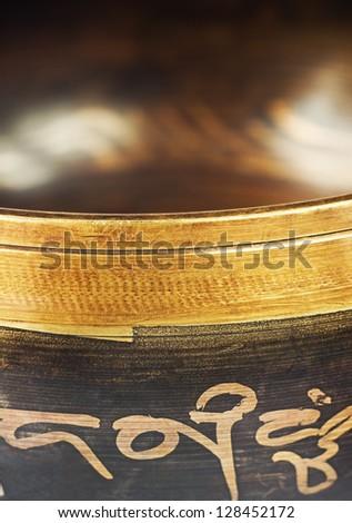 The Tibetan singing bowl on dark close up - stock photo