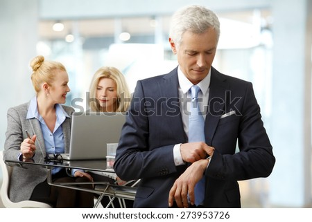 The time is money. Senior businessman standing at office while checking time. Businesswomen sitting in front of laptop and working at background.  - stock photo