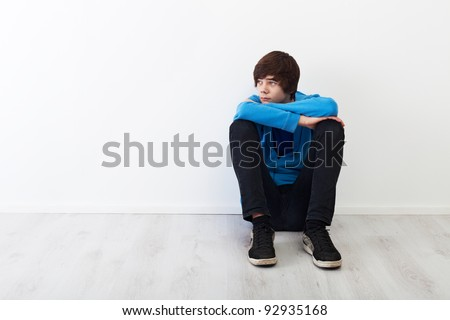 The times when every thought is big - serious teenager boy sitting - stock photo