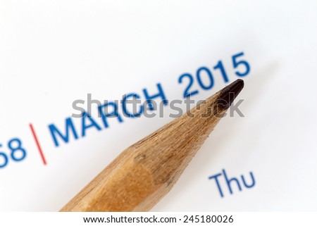 The tip of a pencil point to the year 2015 blur Text on a calendar.