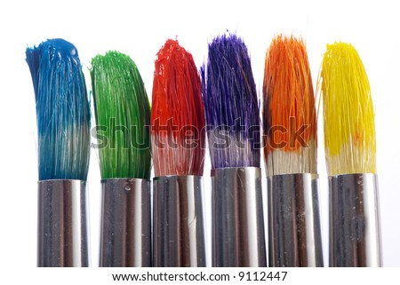 The tips of three colorful paintbrushes ready to be used. - stock photo