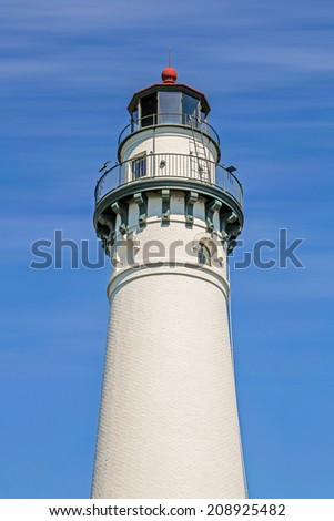 The top of the Wind Point Lighthouse, on the Lake Michigan shore of Racine, Wisconsin, stands tall against a vivid blue sky with wispy white clouds. - stock photo
