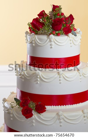 The top tiers of a butter cream wedding cake with fresh red roses on top and red ribbon encircling each layer. - stock photo