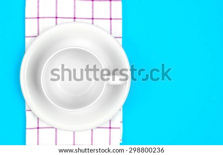 the top view of empty  red dish and towel on vibrant blue color background - stock photo
