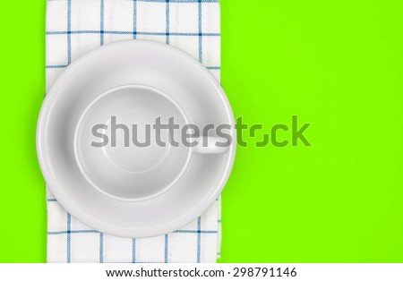 the top view of empty  red dish and towel on vibrant green color background - stock photo