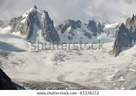 the tour ronde (l) and the mont blanc de tacul (r) above thevallee blanche on the Mont Blanc above chamonix in the french alps. The tiny cable cars give scale - stock photo