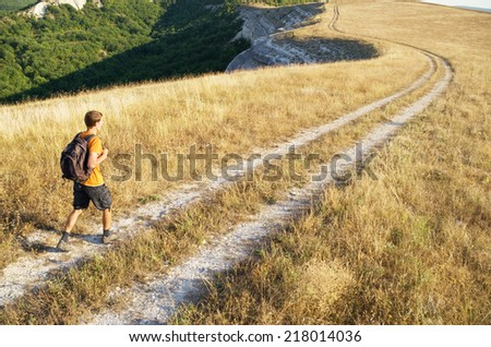 The tourist with a backpack at road in the mountain - stock photo