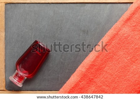 The towel and small size of shampoo bottle on slateboard floor surface represent the toiletry material and travel industry concept related idea. - stock photo